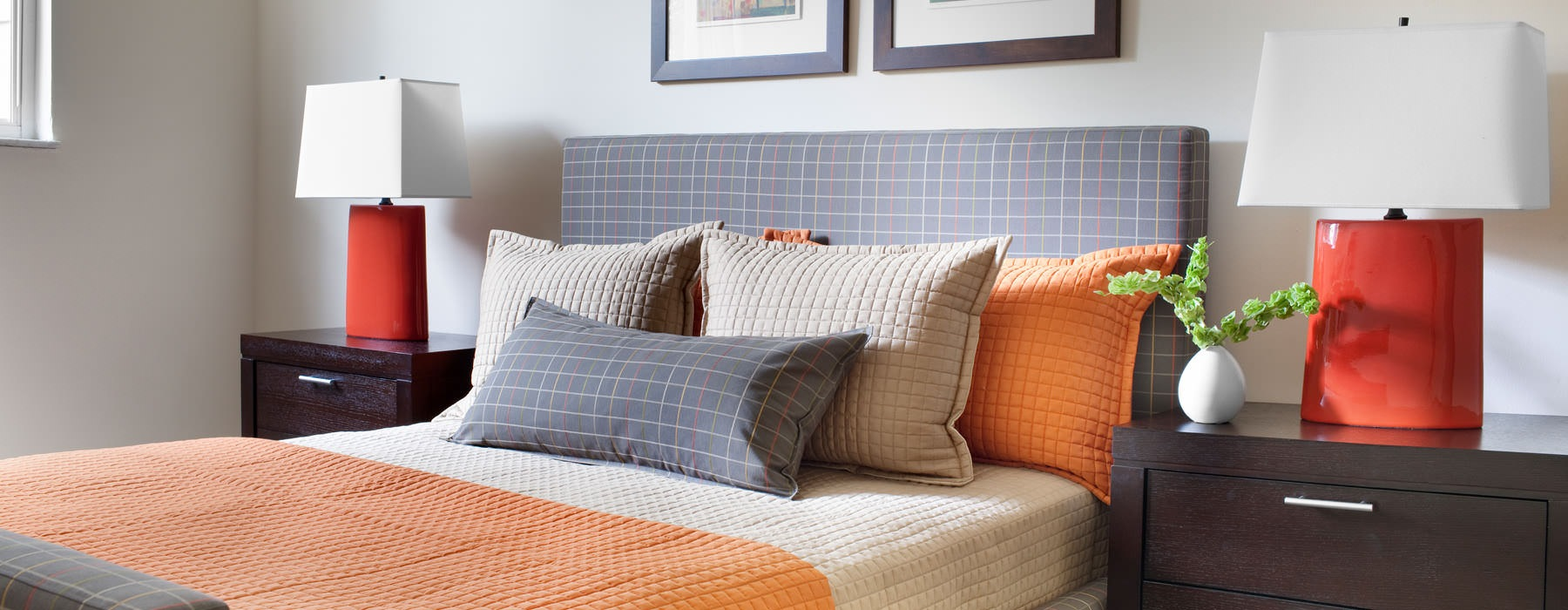 Bedroom with grey bed and orange, grey, and tan pillows
